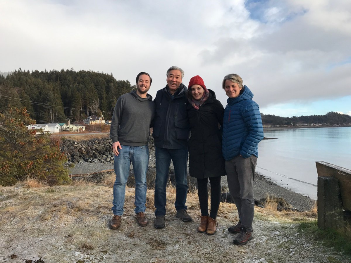 four people standing on a beach in the wintertime