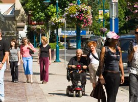 downtown street with people walking, talking and using a mobility scooter